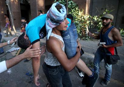 פינוי נפגעים בעימותים אתמול. המהומות התחדשו לפנות בוקר (צילום: AP)