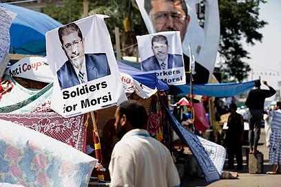 מחנה התומכים של מורסי בקהיר. גם הצבא תלה שלטים משלו (צילום: AP)