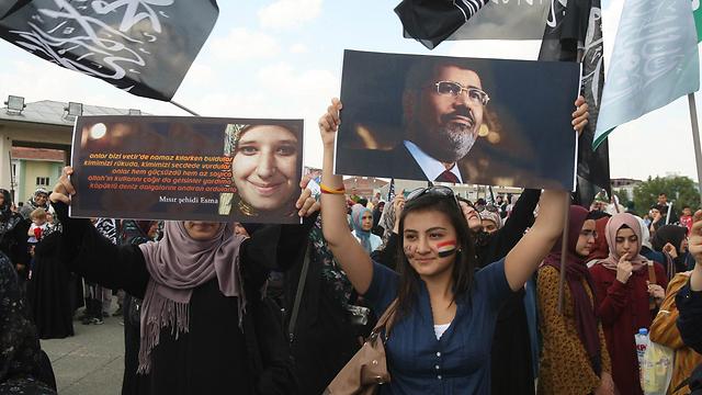 מפגינות באנקרה מניפות תמונת הנשיא המודח מורסי (צילום: AFP)