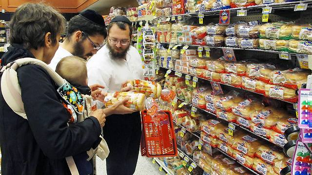 Dovid Lepkivker and Eli Chaikin inspect packages of bagels with Mary Semple and her grandson Levi Weitner in a grocery store in Helena, Mont (Photo: AP)